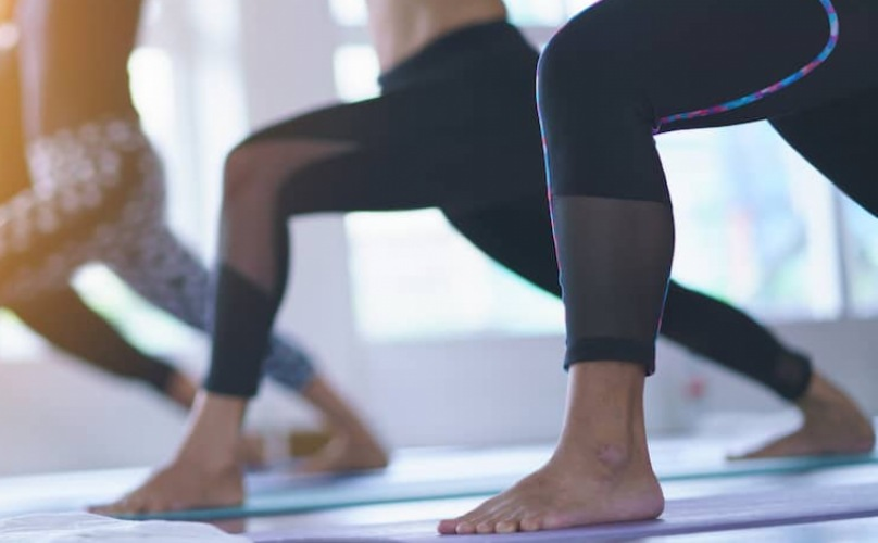 lifestyle image of people doing yoga stretches in a well-lit room