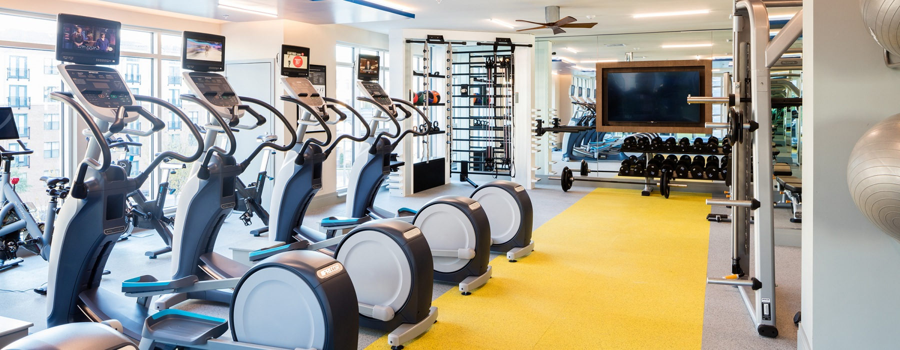 fitness center featuring crossfit equipment, free weights, cardio machines