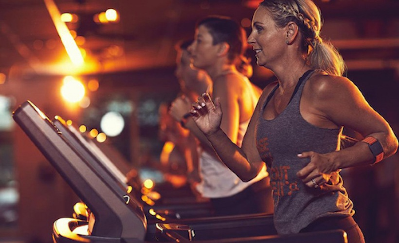 lifestyle image of a woman with others running on treadmills